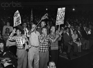15 Nov 1960, New Orleans, Louisiana, USA --- At a meeting of the White Citizens Council of Greater New Orleans - a body formed in opposition to the idea of school desegregation - some members stand, wave Confederate flags and one holds a sign threatening the Federal judge, school board president, and mayor with deportation to Cuba. --- Image by © Bettmann/CORBIS